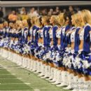 The Cowboys Cheerleaders stand during the National Anthem performance